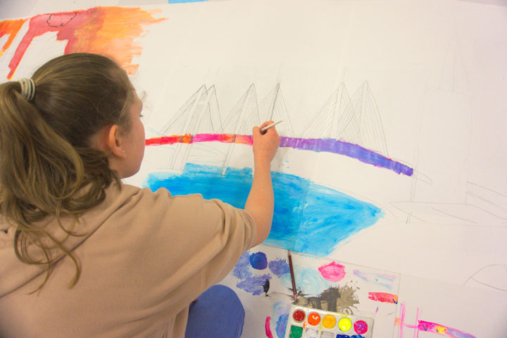 Young artist working on large mixed media piece